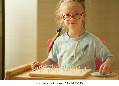 A girl with Down's syndrome develops fine motor skills