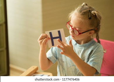 A girl with Down's syndrome is studying the alphabet