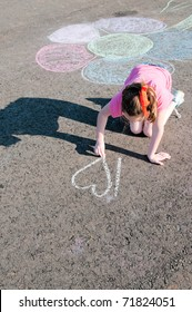 girl drawing with chalk on playground