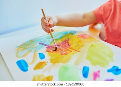 Girl drawing with colorful aquarelle paints at home, in kindergaten or preschool. Creative games, education and distance learning for kids. Stay at home entertainment