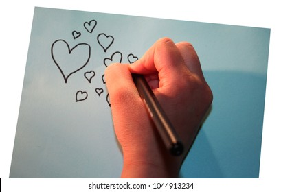 Girl drawing hearts to a blue paper