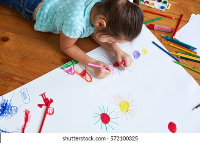 girl drawing on a large sheet of white paper