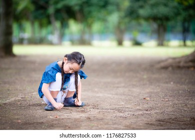 Girl drawing a picture on the ground