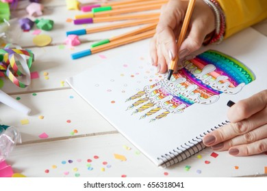 The girl draws a cake with bright colored markers. Gifts, rosettes, confetti and festive accessories.