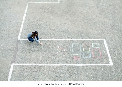 Girl draws chalk house / building