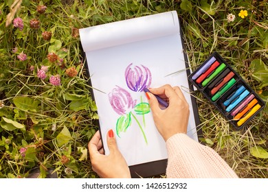 Girl draws clover flower with crayons. Talent inspiration creation and self expression concept