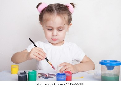 Girl draws in color paints