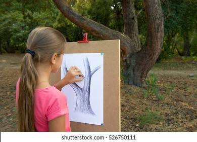 Girl draws in the park. girl paints on an easel in the drawing lesson. Girls Hand draws a pencil tree trunk on a white sheet. Drawing lesson at art school, in the park Drawing from nature.