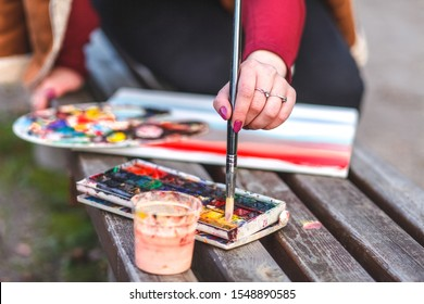 Girl draws a picture while sitting on a bench in a park. The painter mixes paints in order to paint a picture
