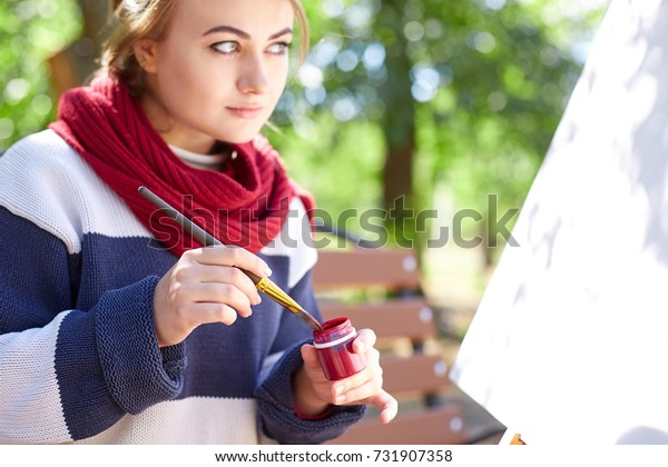 Girl draws red paints close-up on an easel