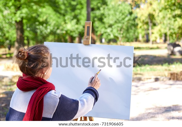 The girl draws red paints on the easel