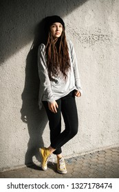 girl with dreadlocks in a black hat near the concrete wall