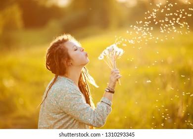 Girl in dreadlocks blowing dandelion on a summer day