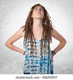 Girl with dreadlocks looking up over textured background