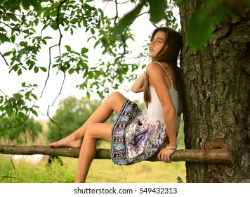 a girl dreaming and sitting under tree in summertime rural place