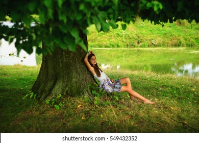 a girl dreaming under tree in summertime rural place