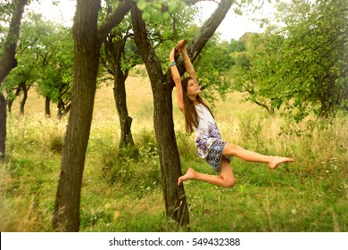 a girl dreaming under tree in summertime rural place. holding on the branch