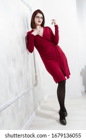 girl in the dress is leaning against the wall