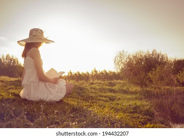 Girl in dress reading book. Morning field.