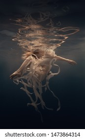 Girl in a dress with ribbons swims underwater