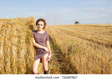 girl in a dress and rubber boots is standing in a field near a stack of straw