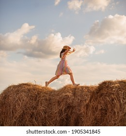 A girl in a dress runs on haystacks in the field. spread hands and beautiful clouds