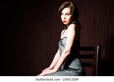 Girl in dress sitting on a chair