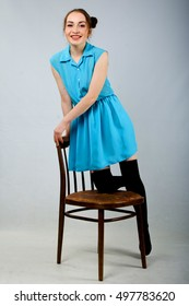 girl in a dress sitting on a chair