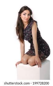 Girl in dress sitting on a cube posing in studio
