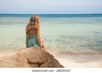girl in dress sitting on a stone by the sea