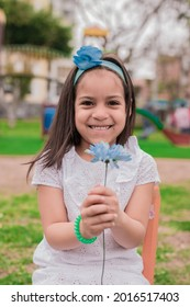 girl in dress sitting in a park with a flower in hand - Shutterstock ID 2016517403