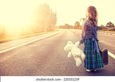 The girl in a dress with a suitcase looking at the sun