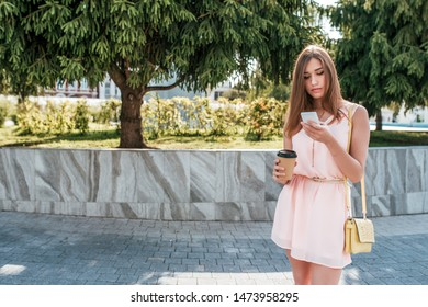 girl in dress, in summer city, stands her hand phone, reads message, online chat, Internet social networks, free space for text, cup of coffee, smartphone, background trees. Long hair tanned skin