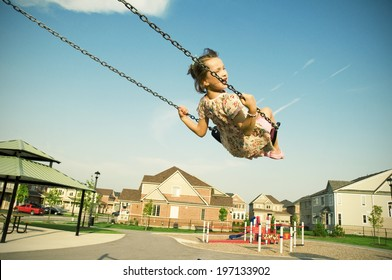 A girl in a dress swinging on a swing.
