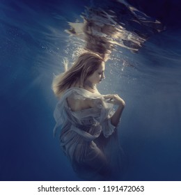 Girl in a dress under the water