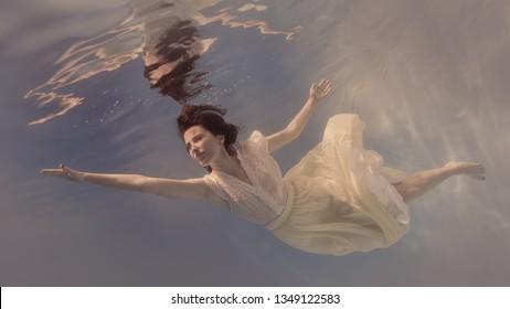 Girl in dress under water
