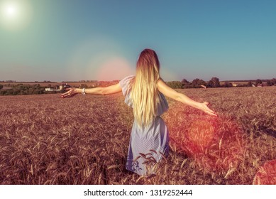The girl in the dress view from the back, walks in the summer in a wheat field. With long dyed hair, arms spread apart. The concept of freedom of joy of discovery and fresh air in nature.