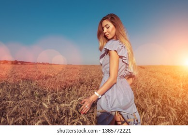 The girl in a dress, walks in the summer in a wheat field. Happy resting in nature. Bright sunny day, with long hair, the lifestyle of a woman.