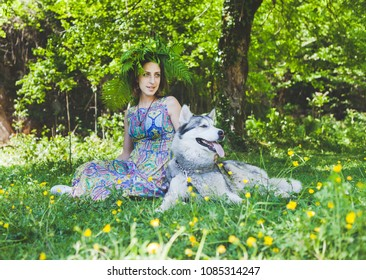 A girl in a dress and a wreath in a green forest sits together with a husky dog. Concept of pets in nature.