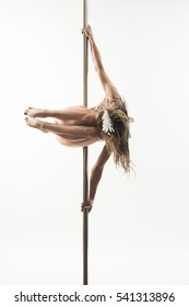 Girl, dressed  angel outfit, makes pole dance exercise