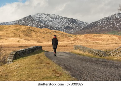 Girl dressed in black wearing a scarf walks away on a road near the Bridge of Orchy, Argyll and Bute, Scotland, UK, where snowy mountains can be seen on a distant valley on the background.