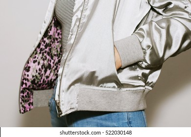 Girl dressed blue jeans, striped body suit, metallic colored bomber jacket. White background.