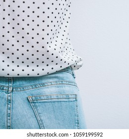 Girl dressed blue jeans and white t-shirt with black peas pattern. Copy space.