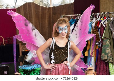 Girl dressed as butterfly stands with hands on hip and smiles at the camera