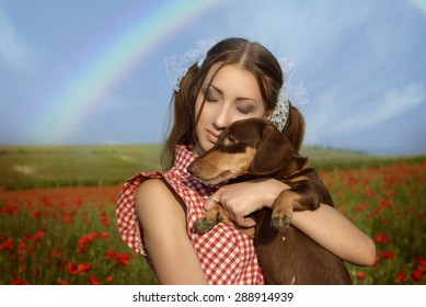 Girl dressed up as Dorothy from Oz. poppy field. With the dog on the hands and the rainbow