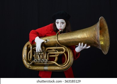 the girl dressed like a MIME playing a wind pipe