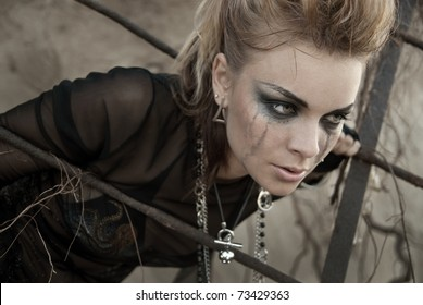 The girl dressed and make-up in rock style. Make-up after tears. She is upset and thoughtful, does not know what to do.