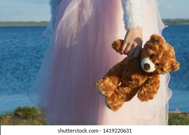 A girl, dressed in a pink skirt, stands on the shore of a reservoir and holds a toy bear in her hand.