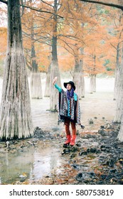 The girl dressed in a poncho pictures of herself in a cypress grove