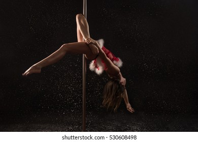 Girl dressed santa outfit makes pole dance  exercises